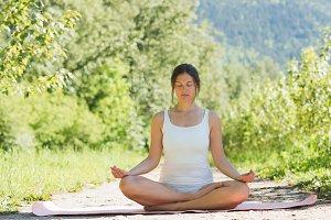 Woman doing meditation pose on yoga mat