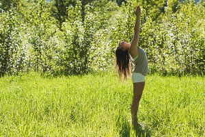 Beautiful woman doing yoga in a green forest