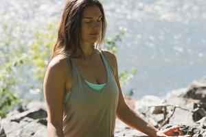 Woman doing meditation on rock near river side