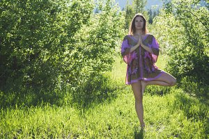 Woman doing yoga tree pose in forest