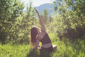 Woman doing yoga in a green forest