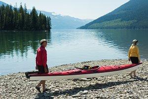Mature couple carrying kayak during sunny day