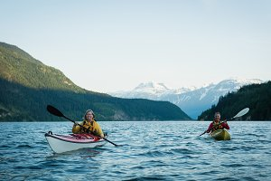 Couple in kayak over lake against sky