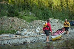Couple carrying kayak in lake
