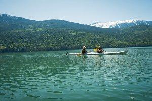 Side view of mature couple kayaing in lake