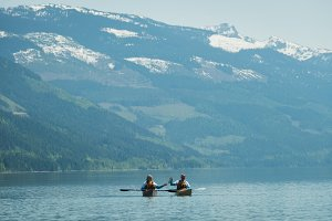 Couple kayaking in lake against snow capped mountain