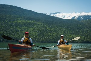 Couple wearing life jackets while kayaking in lake