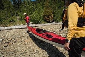 Couple carrying kayak while standing on rocks