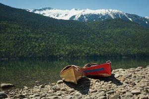 Kayaks at lakeshore against snowcapped mountain