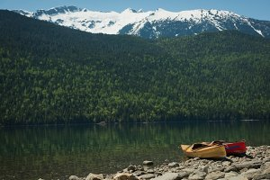 Kayaks at lakeshore against mountain