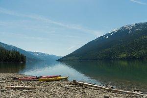 Kayaks at lakeshore against sky