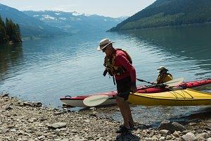 Man carrying kayak at lakeshore