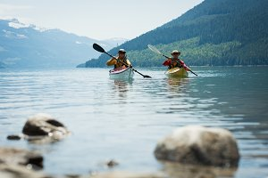 Couple in kayak over lake by mountains