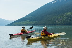 Couple kayaking against mountain