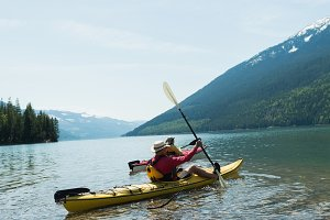 Mature couple kayaking in lake against sky