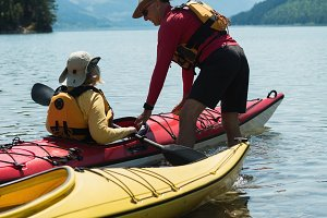 Mature man assisting woman for kayaking