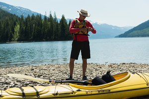 Man wearing life jacket while standing by kayak at lakeshore