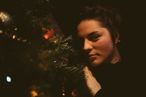 Pretty young girl dreaming of Christmas as she rests. A beautiful woman lies under a Christmas tree and enjoys loneliness