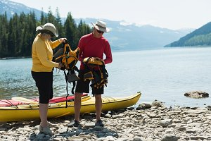 Mature couple with life jacket standing at lakeshore