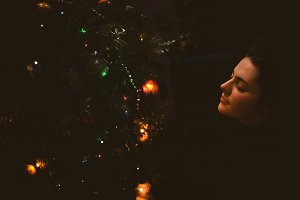 Pretty young girl dreams about Christmas as she is resting. A beautiful woman lies under a tree and sleeps