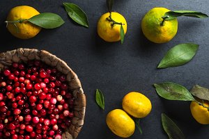 Frame of yellow tangerines and cranberries in a basket