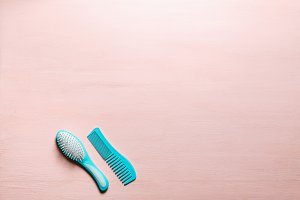 Two Turquoise hair comb crest brushes with handle for all types, isolated on pink copy space background. Minimalistic feminine flat lay.