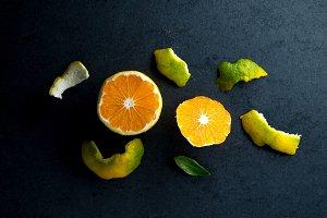 Peeled yellow mandarin and peel on a gray table