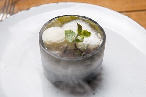 ice cream sweet dessert on a white plate on a wooden table in an Italian retor. Ingredients white ice cream with mint and cocoa in a transparent tequal glass with smoke.
