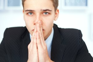 sad praying businessman in office
