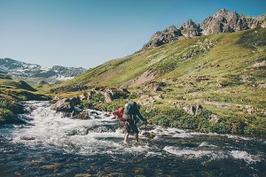 Traveler Man crossing river