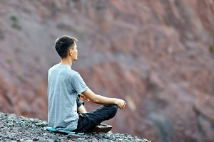 man in yoga position on rocky cliff