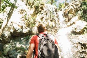 traveler next to the waterfall
