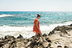 girl in a red dress on the shore