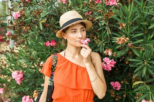 girl with a hat at pink flowers