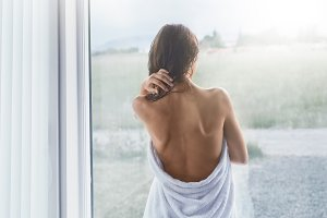 young slender woman stands at a window wrapped in a towel