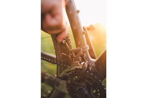 hand with a bicycle tool was engaged in fixing a bicycle outdoors at sunset