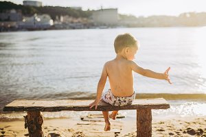 cute baby boy on a bench outdoors on the beach with views of the sea or the water of the sea on a sunny day.