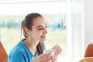 young woman having breakfast in the kitchen