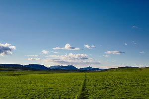 Beautiful Icelandic landscape with green fields mountains, sky and clouds.