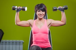 Gym woman strength training lifting dumbbell weights in shoulder press exercise. Female fitness girl exercising indoor in fitness center.
