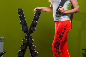 Female fitness trainer in gym line up weights, concept