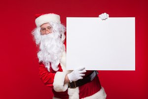 Santa Claus pointing in blank advertisement banner isolated on red background with copy space