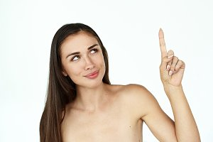 Dreamy woman shows a finger up