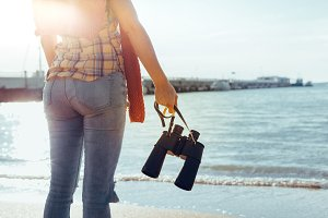 unrecognizable young girl in jeans and a shirt with binoculars in her hand is standing on the beach and enjoying the view and the environment