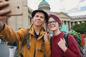 Young couple of tourists taking selfies against the Kazan cathedral in Saint-Petersburg