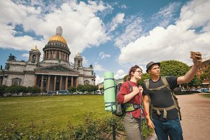 Young couple of tourists taking selfies against the Isaac cathedral in Saint-Petersburg