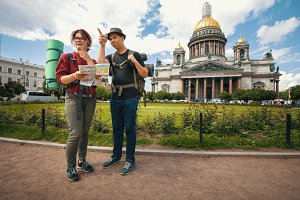 Young tourists check the route on the paper map in landmark of Saint Petersburg, Russia