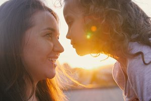Portrait of happy mother and little daughter over sunset