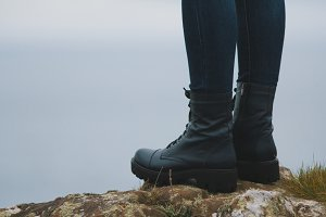 Woman hiker legs in big boots on mountain peak cliff