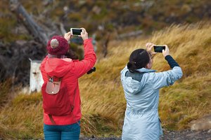 Two hiking chinese women friends use smartphone taking photo in the autumn mountains